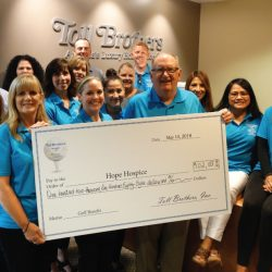 The Toll Brothers holding a check for $102,188 for Hope Hospice at charity Golf Castlewood Country Club
