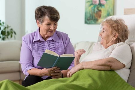 Hope Hospice's elderly volunteer is reading a book to another elderly woman