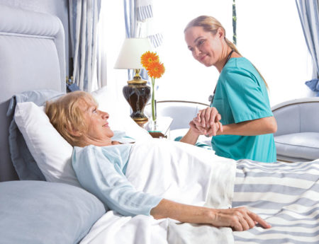 Nurse holding elderly woman's hand while in bed
