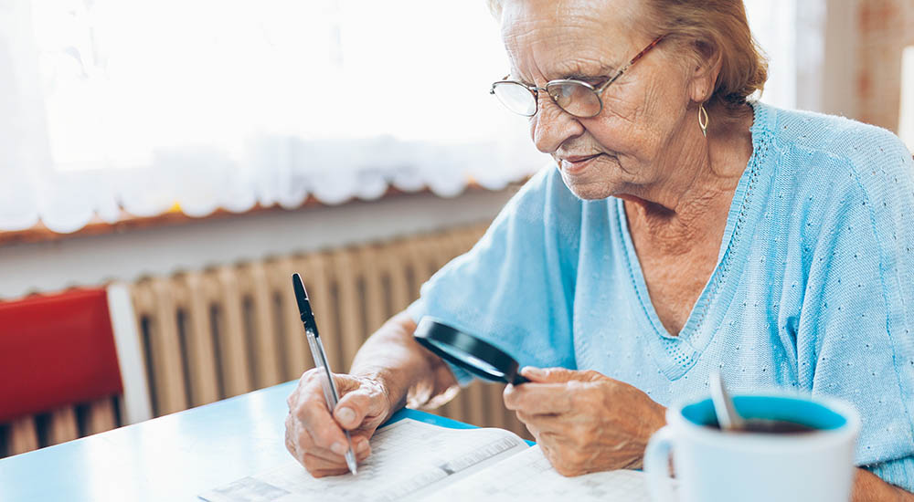 woman using magnifying glass to help read