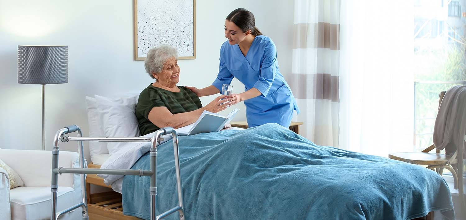A nurse tends to a patient in bed.