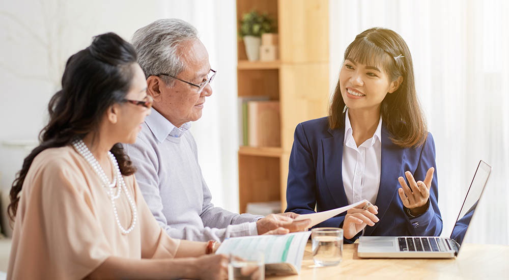 Senior couple speaking with estate planner at kitchen table