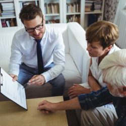 Senior couple speaking with estate planner in living room