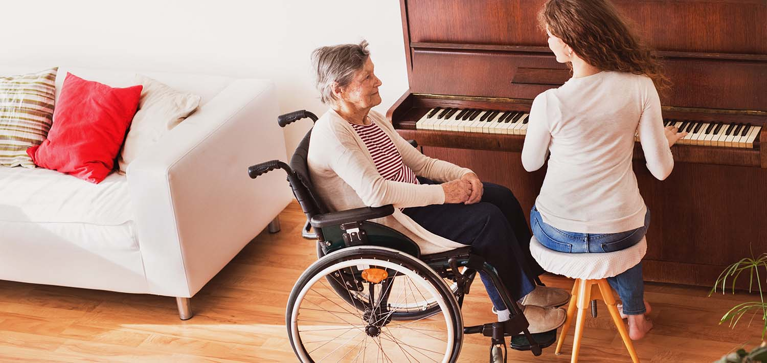 A woman in a wheelchair sits beside a piano player.