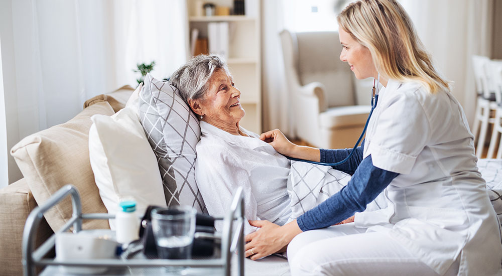 home visit nurse checking on female senior patient