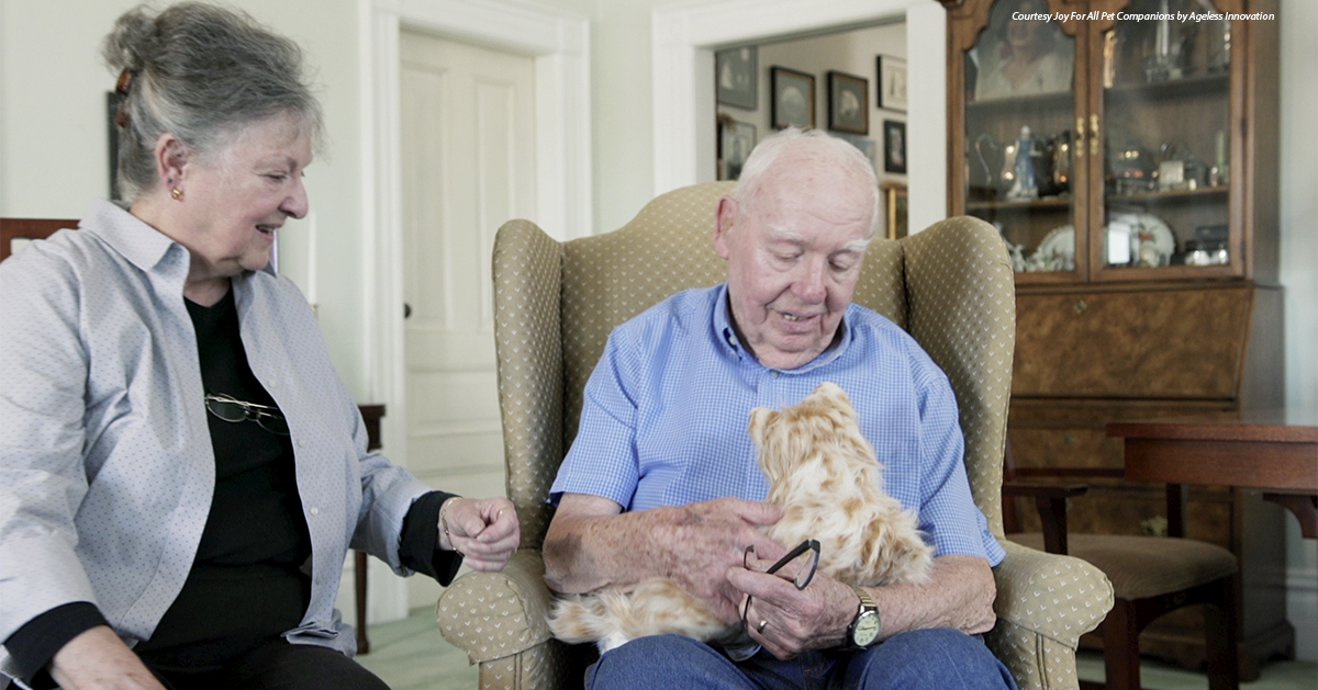 An animatronic cat is presented to an elderly man.